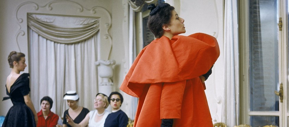 Model wearing Balenciaga orange coat as I. Magnin buyers inspect a dinner outfit in the background, Paris, France, 1954 -® Mark Shaw, mptvimages.com.jpg